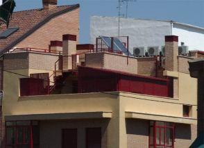 Terraza con carpinterías de aluminio, placas solares y aparatos de aire acondicionado. Foto El País